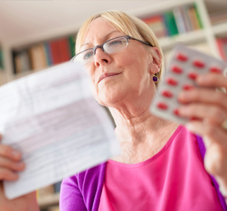Woman reading medication information with pill pack